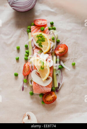 Raw salmon fillet with fresh vegetables ready for cooking 'on papillote'. - Stock Photo