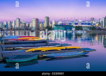 Moored dragon boats and Yaletown condos, False Creek skyline,  Vancouver, British Columbia, Canada, - Stock Photo