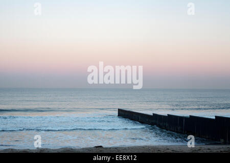 Sunrise at Tijuana beach in Mexico, showing the the US - Mexican border fence running into the Pacific Ocean. - Stock Photo