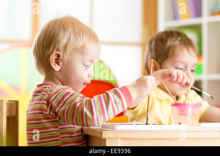 smiling kids playing and painting - Stock Photo