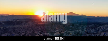 Sun rising with hot air balloon in foreground. - Stock Photo