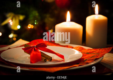 Christmas decoration, candles, cinnamon sticks and pieces of orange, on christmas tree background - Stock Photo