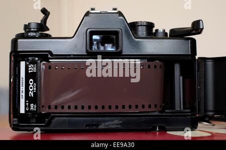 An old slr film camera loaded with a 35mm film cassette - Stock Photo