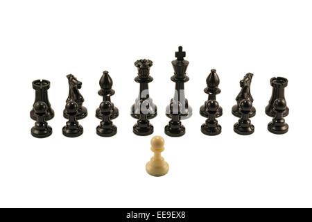 White pawn standing in front of the aligned black chess pieces. - Stock Photo