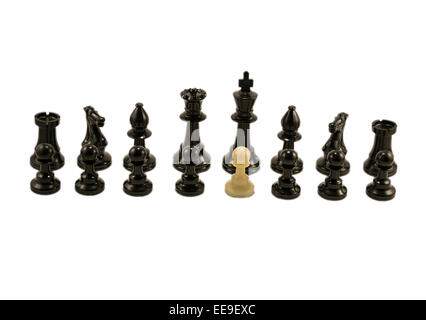White pawn standing alongside the chess black pieces - Stock Photo