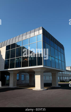 Glass fronted new building on pillars in courtyard on a bright sunny day - Stock Photo