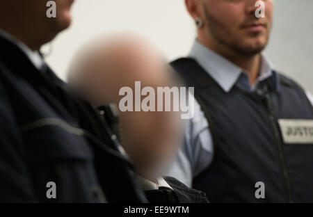 A defendant stands between justice officials before the start of the trial against four neo-Nazis at the district - Stock Photo
