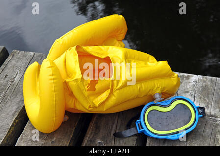 Yellow life jacket and diving mask for children on lake bridge - Stock Photo