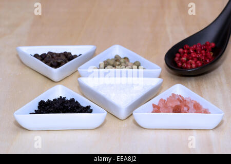 Variety of peppercorns and salt on a table - Stock Photo