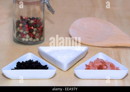 Three types of salt with colored peppercorns and cooking spoon - Stock Photo