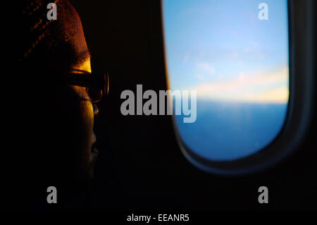 An airline passenger looks out of the window of a Boeing 787 Dreamliner on route from London to Toronto. - Stock Photo