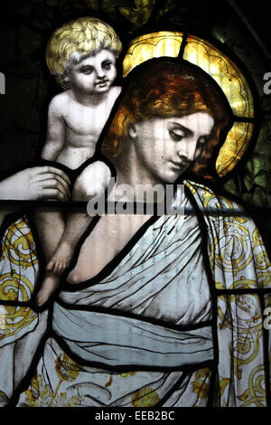 Stained Glass Window Of A Child With A Figure Representing Charity by Designer: Henry Holiday & Firm: James Powell - Stock Photo