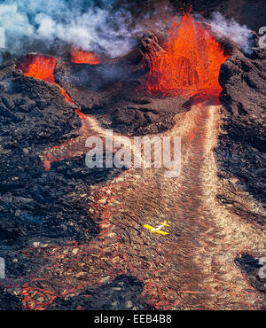 Small airplane flying over the volcano eruption at Holuhraun, Bardarbunga Volcano, Iceland. Picture Date: Sept, - Stock Photo