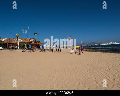 Tourists walking along clean sandy beach tourist resort Corralejo Fuerteventura Canary Islands ferries moored in - Stock Photo