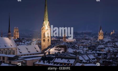 The old town with snow-covered roofs at night, with the illuminated Gothic bell towers, Zurich, Switzerland. - Stock Photo
