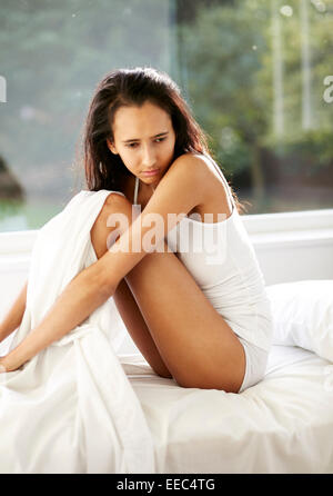 Young girl sat on bed looking sad - Stock Photo