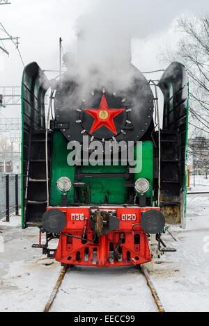 Old steam locomotive at railroad platforn in winter - Stock Photo
