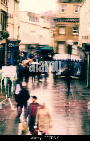 Busy shopping street in Bath, UK on a rainy Saturday afternoon - Stock Photo