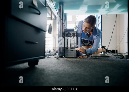 Female assistant working in office, plugging cables to computer and electronic equipment, messing around with wires. - Stock Photo