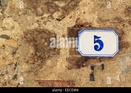 House number 5 on a yellow brick wall - Stock Photo