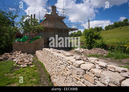 Renovation and new built dry stone wall constructed of new Cotswolds stone using traditional method at period property, - Stock Photo