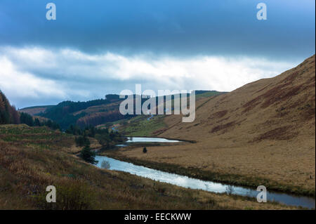 River runs along a valley in the Brecon Beacons mountain range in Wales, UK - Stock Photo