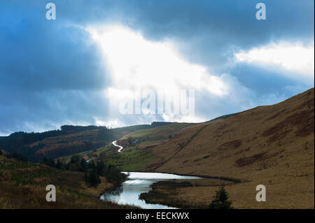 Sunlight through cloud shining on river and empty road along a valley in the Brecon Beacons mountain range in Wales, - Stock Photo