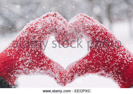 Woman making heart symbol with snowy hands - Stock Photo