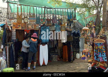 tourist checking the street vendors who selling indian cotton clothes and goods,varkala,papanasam beach,kerala,india,pradeep - Stock Photo