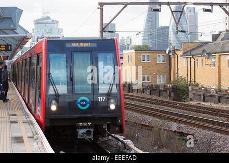 Docklands Light Railway train with London skyline - Stock Photo