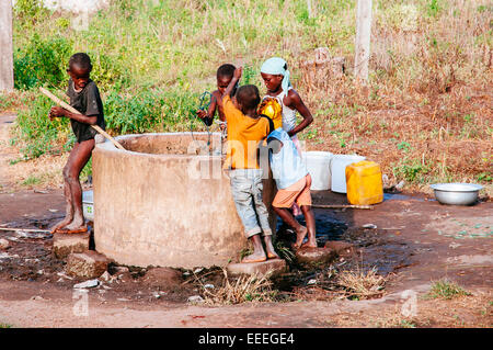 Children collecting water from a well, Ghana - Stock Photo