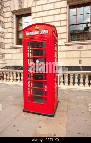 Traditional red telephone box in London UK - Stock Photo