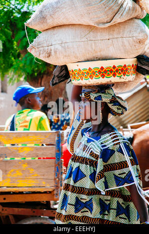 Woman carrying heavy sacks on head and walking on the streets of Djenne, Mali. - Stock Photo