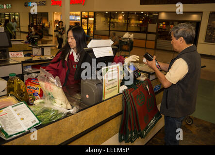 Asian-American woman, cashier, 99 Ranch Market, Pacific East Mall, city of Richmond, Contra Costa County, California - Stock Photo