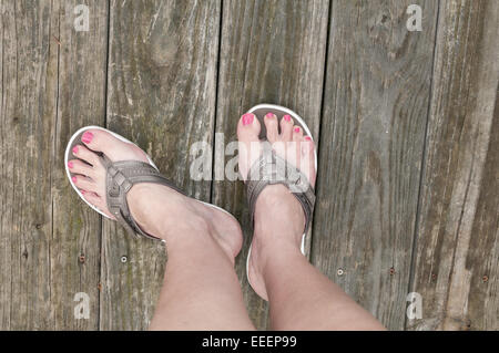 Female feet standing on a wooden deck in a pair of bronze colored sandals or flip flops.