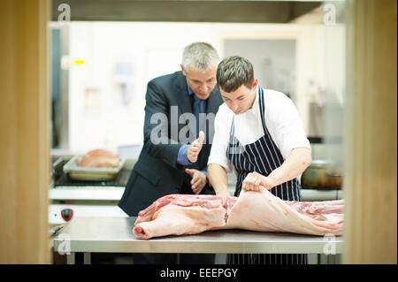 A manager teaching a trainee butcher how to cut meat - Stock Photo
