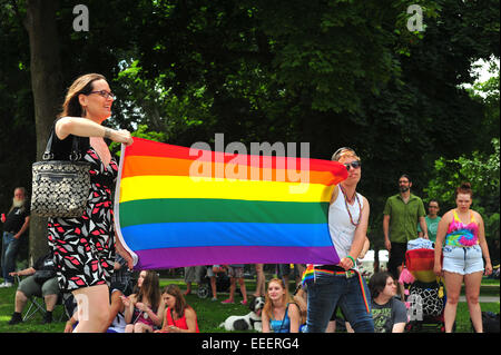 Women carrying the rainbow pride flag during a pride parade in London, Ontario. - Stock Photo