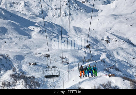 Four people ride the ski lift up the mountain in the Alps, France - Stock Photo
