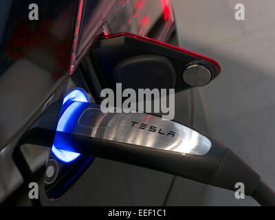 tesla model s plug in electric car plugged into a charging station in stock photo royalty free. Black Bedroom Furniture Sets. Home Design Ideas