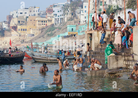 Varanasi, India. Hindus bathing and praying in the Ganges river, early morning - Stock Photo