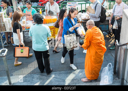 Buddhist monk at Ashok/Sukhumvit junction begging for food receiving alms by praying locals,Bangkok,Thailand - Stock Photo
