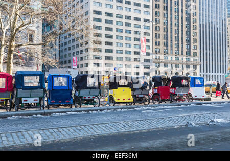 Line of colourful three-wheeled cycle taxis lined up in roadside Manhattan ready for hire for tourist tours of Central - Stock Photo