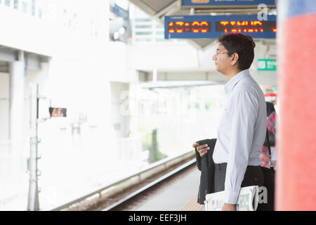 Candid Asian Indian businessman waiting at public train station. - Stock Photo