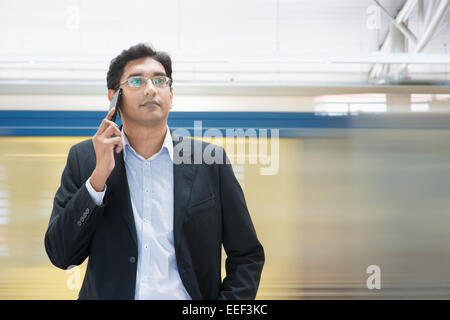 Asian Indian businessman on the phone while waiting train at railway station. - Stock Photo