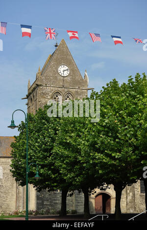 Ste-Mere-Eglise Church and flags of the allied liberators. The church played a role on D-Day, June 1944 - Stock Photo