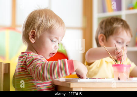 kid painting with paintbrush - Stock Photo