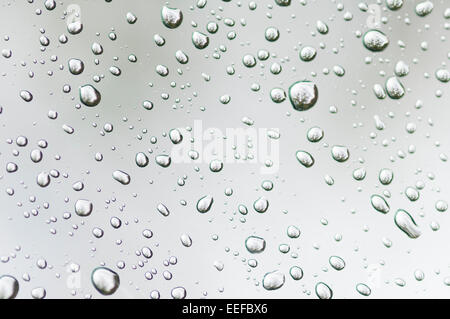 Water droplets on clear glass reflect ambient light producing interesting patterns. - Stock Photo