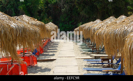 Straw parasols (umbrellas) on a beautiful beach. - Stock Photo