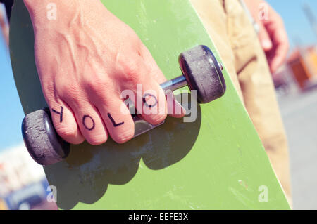 closeup of a young man with the word yolo, for you only live once, tattooed in his hand holds a skateboard - Stock Photo