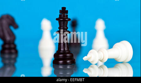 Checkmate - black defeats white on blue background - Stock Photo